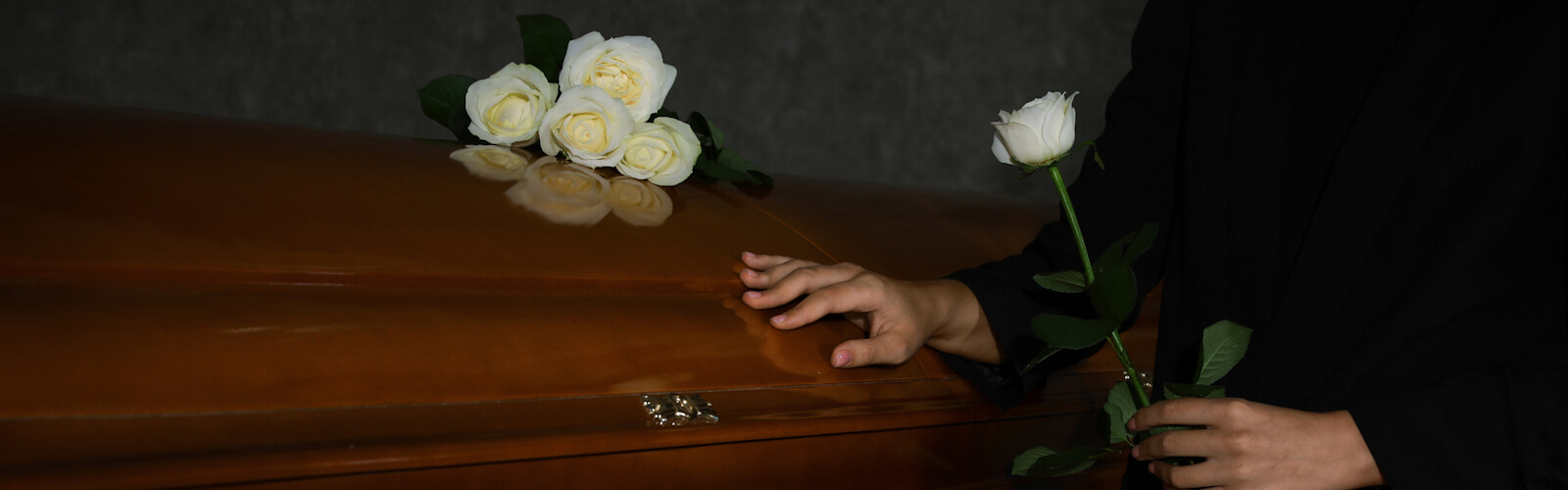 Young woman with white rose near casket in funeral home