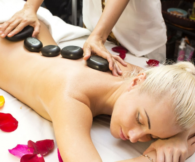 Blonde woman surrounded by petals is laying on her front getting hot stones placed on her back