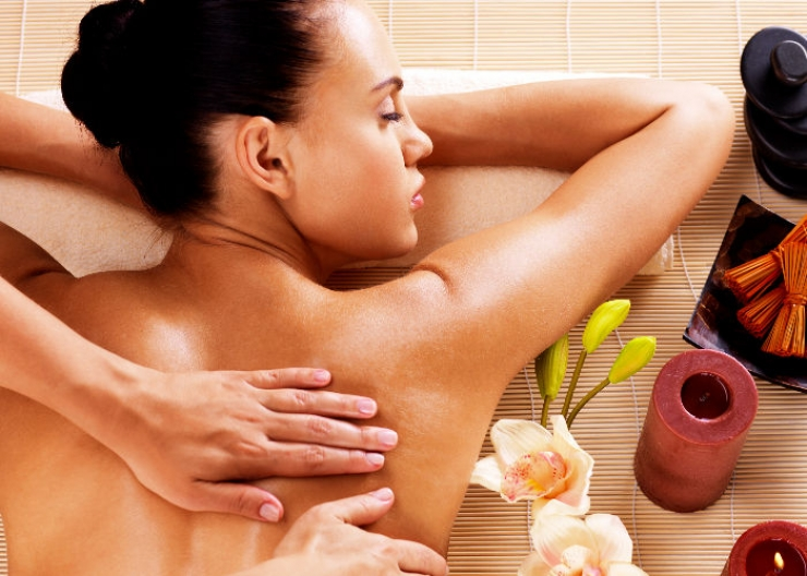 Woman laying next to flowers and candles getting an Aromatherapy back massage