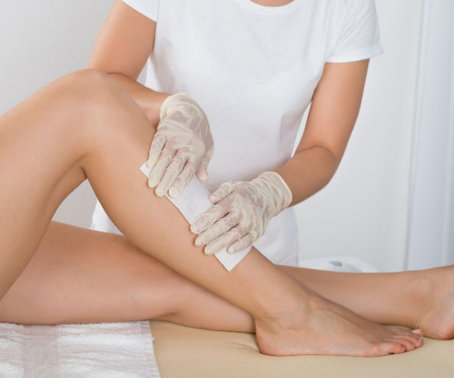 woman laying on a towel getting the front of her legs waxed