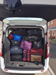 Rear view of a white van taht has been filled with luggage