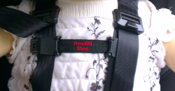 The Houdini Stop simply clips on to each shoulder strap of the harness neatly positioned underneath the Adjusters to help prevent the passenger from separating the shoulder straps in order to escape.