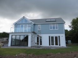 This house is timber frame with blockwork facing , top half covered with cedral boarding .