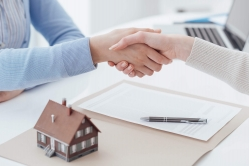 People shaking hands over home insurance