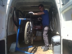 mechanic repairing bicycle in back of van
