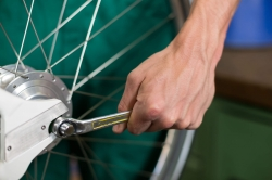 bicycle mechanic working on rear wheel with wrench