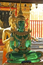 A gold Buddha sitting on a table