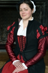 Photo by David Hall (http://www.david-hall-images.co.uk)  This is a 'merchant class outfit, consisting of a red wool kirtle with black velvet trim and satin sleeves, and a black wool gown. C 1570