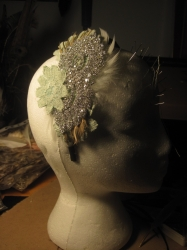 This wonderfully sparkly headpiece was made to coordinate with the Brides dress, the Bridesmaids accessories and the Brides feather fan which she carried in place of a bouquet. The green lace flowers are from the Brides mothers dress. Do you have a piece of family history your would like to incorporate into your dress?  From £65