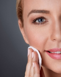 blonde woman with blue eyes applying facial product with a makeup cotton pad