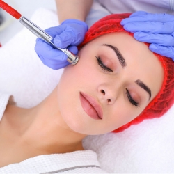 woman laying with red hair net on her head getting a Microdermabrasion facial