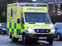 ambulance with warning lights on in traffic