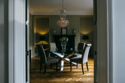 Glinting chandelier and corner lamps creating moody shadows