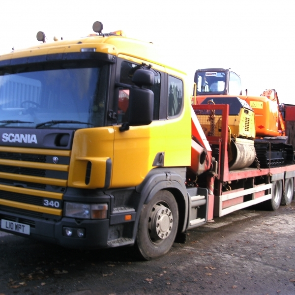 A Modern Mini Excavator on the Back of a Truck for Transport