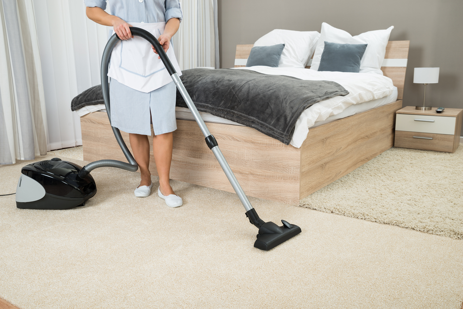 woman hoovering bedroom carpet