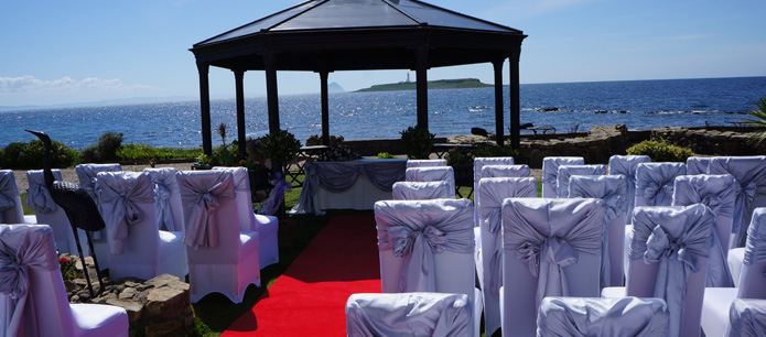 Wedding function complete with purple ribboned chairs and gazebo with an ocean backdrop