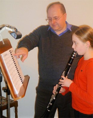 Mark Toomey teaching a girl to play clarinet
