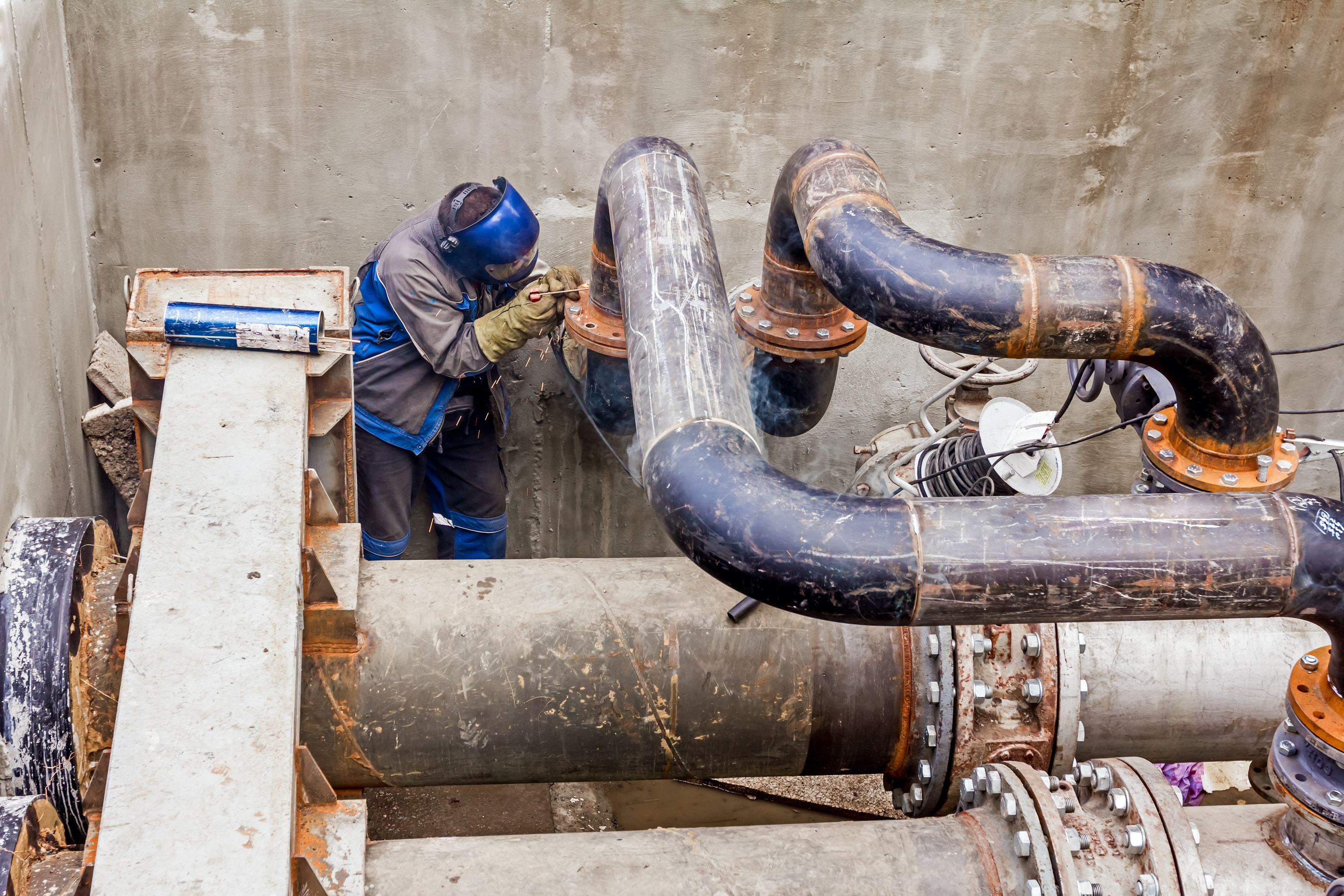 Welder working on pipe joins
