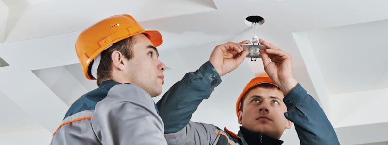 Professional Electricians fitting emergency lighting