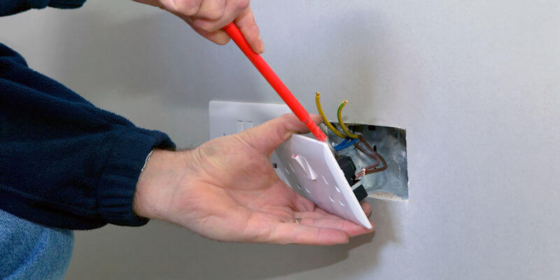 Electrician installing a plug socket