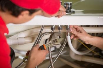 Plumber repairing the plumbing for a bath