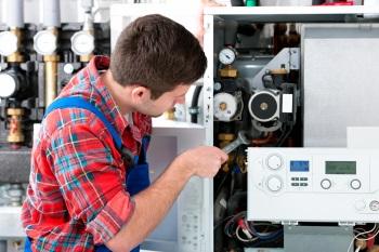 Heating engineer repairing a boiler