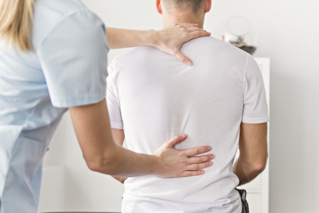 Physiotherapist doing physical back exercises with patient