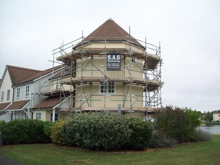 Scaffolding being erected around the exterior of a house