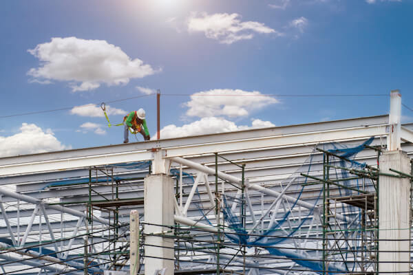 Man working on construction site with scaffold and building with sky background, scaffolding for construction factory