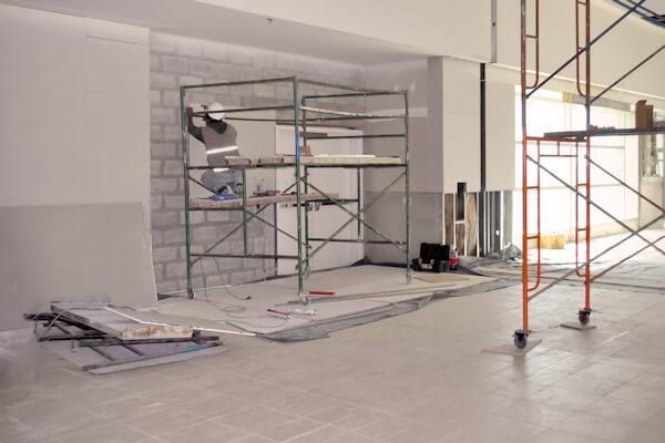 Worker on scaffolding installing gypsum wall