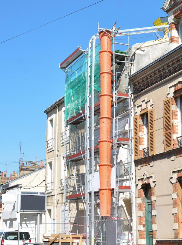 Scaffolding on building with waste chute