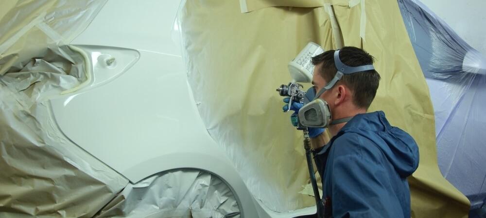 Man Spraying a Car in a Booth